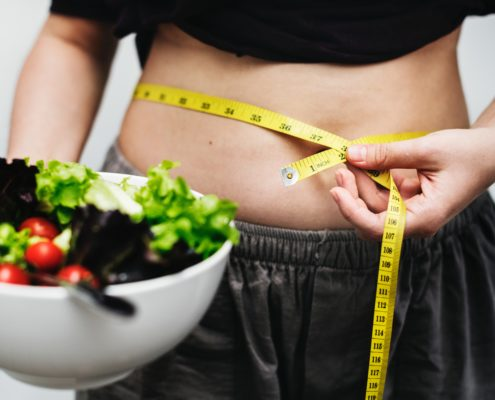 Image of a female with a measuring tape wrapped around her belly and a bowl of salad in hand. Prevent weight gain with the SANE Diet.